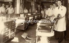 Historische Fotografie aus einem Friseursalon in der Hamburger Neustadt - Friseurstühle mit Lederkissen und Armlehne - Angestellte / Friseure mit weissen Kitteln.