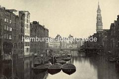 Historische Foto vom der Holzbrücke über den Nikolaifleet zur Hamburger St. Katharinenkirche.  Schuten mit Kohleladung liegen an Dalben, dahinter die hölzerne Reimersbrücke.
