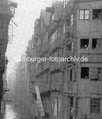 Altes Bild vom Katharinenstraßenfleet in der Hamburger Altstadt - Speichergebäude, Bewohner blicken aus dem Fenster.