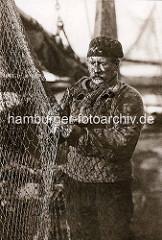 Ein Hochseefischer mit Pfeife aus Hamburg Finkenwerder flickt seine Netze.