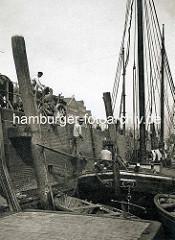 Ewer / Segelschiff im Zollkanal der Hamburger Altstadt - Entladung von Ziegelsteinen per Hand in ein an Land stehendes Pferdefuhrwerk.