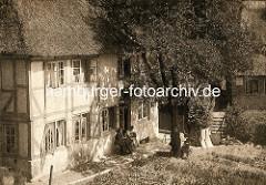 Historische Fotografie vom Krumdal in Hamburg Blankenese - Frauen sitzen in  vor einem Fachwerkhaus mit Reetdach in der Sonne. Die Fenster des Hauses sind zum Lüften geöffnet.