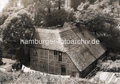 Altes Foto von einem Wohnhaus mit Reetdach in Hamburg Blankenese - Wäsche hängt zum Trocknen auf der Leine.
