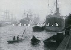 Historische Szene im Hamburger Hafen - Frachschiffe - Dampfschiffe und Segelfrachter - liegen am Kai oder im Hafenbecken; im Vordergrund ein Tuckerboot in Fahrt, daneben ein Ruderboot von Hafenfischern mit Wurfnetz.