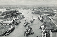 Historische Luftaufnahme vom Rosshafen - Hafenbecken im Hamburger Hafen. Frachter liegen an den Kaimauern und an den Dalben in der Mitte des Hafenbeckens und werden über Schuten und Binnenschiffe entladen.