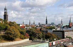 Türme der Hansestadt Hamburg; lks. die St. Michaeliskirche - re. die Schwedische Gustaf Adolfskirche; ein Zug der Hochbahn verlässt die Haltestelle Landungsbrücken.