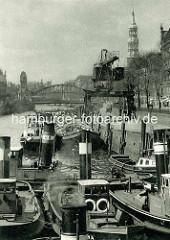 Schlepper mit hohem Schornstein im Zollkanal - Binnenschiffe an der Kaimauer vom Dovenfleet; Portalkran mit Ladung - im Hintergrund die Kornhausbrücke und der Kirchturm der St. Katharinenkirche.