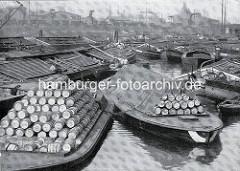 Altes Foto vom Hamburger Billehafen - Schuten mit gestapelten Fässern, abgedeckte Binnenschiffe.