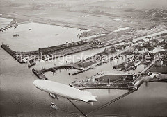 Alte Luftaufnahme des Hafens von Cuxhaven; ein Luftschiff fährt über dem Hafen. Im Hintergrund das Steubenhöft mit dem Amerikahafen und den Auswandererhallen am Kai. Davor die Einfahrt zum Alten Fischereihafen. Im Vordergrund die Seebäderbr