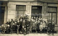 Altes Gruppenfoto mit Kindern vor einem Hauseingang in Hamburg Winterhude - Mädchen mit langen Zöpfen - Jungs mit Mützen, Tretroller und Dreirad - Schäferhund mit Maulkorb.
