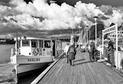 Alsterschiffanleger Uhlenhorster Fährhaus in Hamburg Uhlenhorst an der Aussenalster; Alsterdampfer Saselbek am  Anleger, Fahrgäste steigen in das Fahrgastschiff ein, dichte weisse Wolken am Himmel - Schwarz Weiß Aufnahme.
