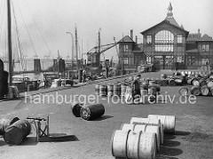 Historische Fischauktionshalle auf dem St. Pauli Fischmarkt in Hamburg.  Fässer liegen auf dem Platz - links eine Waage. Fischerboote haben am Kai festgemacht - im Hintergrund ein Kran und die Wassertreppe vom St. Pauli Fischmarkt.