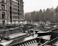 Schuten und Barkassen im Nikolaifleet in der Altstadt Hamburgs - Ewerführer staken ihre Boote durch das Fleet.