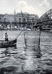 Hafenfischer mit Wurfnetz an der Überseebrücke im Hamburger Hafen - im Hintergrund die Hochbahn am Baumwall und die Kirchturmspitze der St. Micheliskirche.