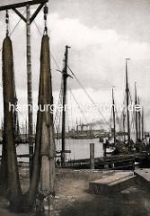 Historische Fotografie vom Hochseehafen in Cuxhaven - im Vordergrund hängen Netze zum Trocknen.
