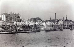 Alte Ansicht der Fischauktionshalle in Altona - Anleger mit Booten am Elbufer; re. im Hintergrund der Kirchturm der St. Pauli Kirche.