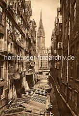 Foto vom historischen Hamburg - im Steckelhörnfleet liegen abgedeckte Schuten - geöffnete Fenster in den Wohnhäuser, Wäsche zum Trocknen hängt vor den Fenstern. Im Hintergrund die Reimersbrücke und der Kirchturm der St. Nikolaikirche.