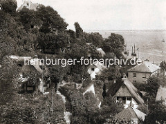 Historische Fotografie von Wohnhäusern - Reetdachhäusern im Treppenviertel von Hamburg Blankenese - im Hintergrund die Elbe.