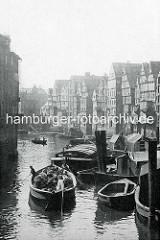 Altes Foto vom Nikolaifleet, re. die Kaufmannshäuser / Speicher an der Deichstraße; Schuten und Arbeitsboote im Fleet - ein Holzboot beladen mit Körben wird von den Schiffsführern durchs Wasser gestakt.