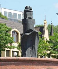 Denkmal Madonna der Seefahrt am St. Pauli Fischmarkt auf der Hochwasserschutzanlage. Dahinter die Fassade eines historischen Gebäudes an der Strasse.