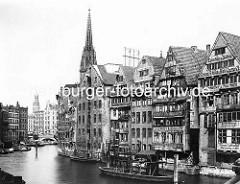 Blick in das Nikolaifleet in der historischen Hamburger Altstadt - Speicher und Wohngebäude am Fleet; im Hintergrund die Holzbrücke und der Kirchturm vom Hamburger Rathaus und der Kirchturm der St. Nikolaikirche.