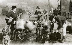 Milchhändler mit Karre und Milchkannen bei den Hamburger Landungsbrücken - die Zughunde tragen Maulkörbe.