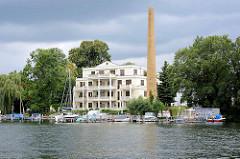 Einzelnd stehender ehem. Fabrikschornstein - mehrstöckiges Wohnhaus mit Balkons / Terrassen; Bootsliegeplätze am Spreeufer in Berlin.