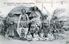 Historisches Foto einer sogen. Völkerschau in Hamburg Hagenbecks Tierpark in Stellingen; Habr Auel Häuptling aus Äthopien mit Familie; Strohütte mit Palmen.