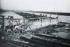 Historische Aufnahme vom Bau der Kaimauer im Kuhwerder Hafen / Hafenbecken vom Hamburger Hafen. Bauarbeiter schieben Loren mit Baumaterial auf den Gleisen entlang der Baustelle.