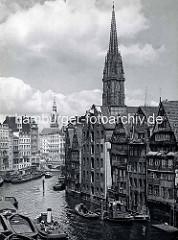 Blick von der Hohen Brücke auf das Nikolaifleet in der Alstadt Hamburgs - re. Rückseite von Speichergebäuden an der Grimm - im Hintergrund ein Ausschnitt der Holzbrück und der Turm vom Hamburger Rathaus - re. der Kirchturm der St. Nikolaikirche