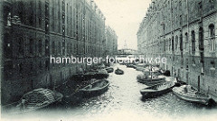 Historisches Foto vom Kehrwiederfleet mit Blick Richtung Elbe;  Schuten beladen mit Säcken liegen an den Speichern; Säcke werden mit Winden in das Lager hinaufgezogen.