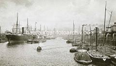 Altes Bild vom Segelschiffhafen in Hamburg - Frachtschiffe liegen an Dalben im Hafenbecken; Schuten und Elbkähne haben am Asiakai festgemacht.