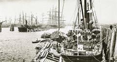 Arbeit im Hafen Hamburgs - altes Bild aus dem Hansahafen; ein Frachter wird über Schuten / Binnenschiffe  be- oder entladen.