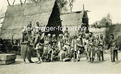Altes Foto von der Völkerschau in Hagenbecks Tierpark in Hamburg Stellingen - Gruppe von Kannibalen sitzen und stehen vor ihren Hütten.