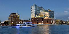 Blaue Stunde über der Elbe bei der Hamburger Hafencity - ein Fahrgastschiff fährt elbaufwärts; beleuchtetes Konzerthaus Elbphilharmonie und Bürogebäude am Kehrwieder.