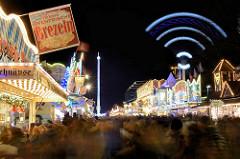 Hamburger Dom bei Nacht, Langzeitbelichtung; Stand mit Brezeln - Riesenschaukel in Bewegung.