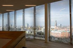 Ausblick auf das Hamburg Panorama durch ein Fenster der Elbphilharmonie. Blick auf die Hamburger Neustadt mit Baumwall und St. Michaeliskirche.
