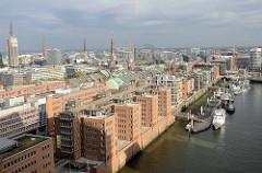 Blick auf den Sandtorhafen / Traditionsschiffhafen in der Hamburger Hafencity. Bürogebäude und Wohnhäuser am Wasser - im Hintergrund die Kupferdächer der Hamburger Speicherstadt und Kirchtürme Hamburgs.