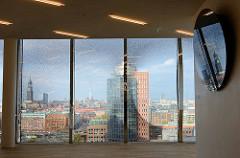Ausblick auf das Hamburg Panorama durch ein Fenster der Elbphilharmonie - im Vordergrund der Büroturm am Kehrwieder + lks. der Kirchturm der St. Michaeliskirche ehem.? Wahrzeichen der Hansestadt Hamburg.
