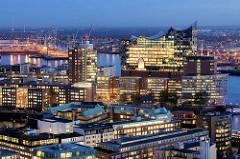 Abendstimmung in Hamburg - Blick über die Hamburger Altstadt zur beleuchteten Elbphilharmonie und den Bürogebäuden am Kehrwieder; im Hintergrund die Norderelbe und der Hansahafen.