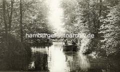 Historische Aufnahme vom Rodenbeker Quelltal in Hamburg Bergstedt; Bäume dicht am Wasser - ein Holzboot wird mit einer Stange gestakt - Mann mit Strohhut.