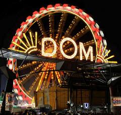 Beleuchteter Schriftzug Dom über dem Eingang am Holstenglacis - Riesenrad in Bewegung, Langzeitaufnahme.