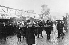 Historische Fotografie vom Hamburger Dom - Männer mit Hüten, Melonen; Schilder - Lebend zu sehen! Der grösste und der kleinste Mensch der Welt - hier die Atzteeken.