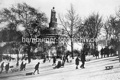 Alte Fotografie von Hamburg im Winter - Kinder rodeln am Alten Elbpark, im Hintergrund das Bismarckdenkmal.