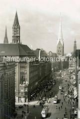 Historische Fotografie von der Mönckebergstraße in der Hamburg Innenstadt / Altstadt; Straßenbahnen, PKW und Fahrradfahrer. Lks. der Kirchturm der St. Jakobikirche und St. Nikolai - re. die Petrikirche und der Hamburger Michel.