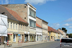 Unterschiedliche Baustile - Geschäfte und Wohnhäuser in der Karl Marx Straße von Neuruppin.
