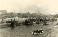 Ponton mit wartenden Fahrgästen an der Überseebrücke; Barkassen und Tuckerboot in Fahrt - im Hintergrund die Hamburger Speicherstadt und die Einfahrt zum Sandtorhafen.