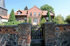 Pfarrhaus - Backsteingebäude mit Kreuz im Giebel - Einfriedung durch Feldsteinmauer und Holztor in Karwe / Neuruppin.