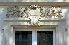 Fassadendekor - Blattwerk über einem Fenstersturz eines Wohnhauses in Neuruppin.