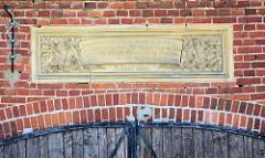 Inschrift an der Fassade der Scheune des ehem. Gutshofs in  Karwe, Gemeide Karstädt. Inschrift: Was draußen reif und trocken ist das fahre ein zur Scheune. Das Stroh verwerte Du als Mist das Korn betracht als Deine, und gib davon mit frohen Sin  dem